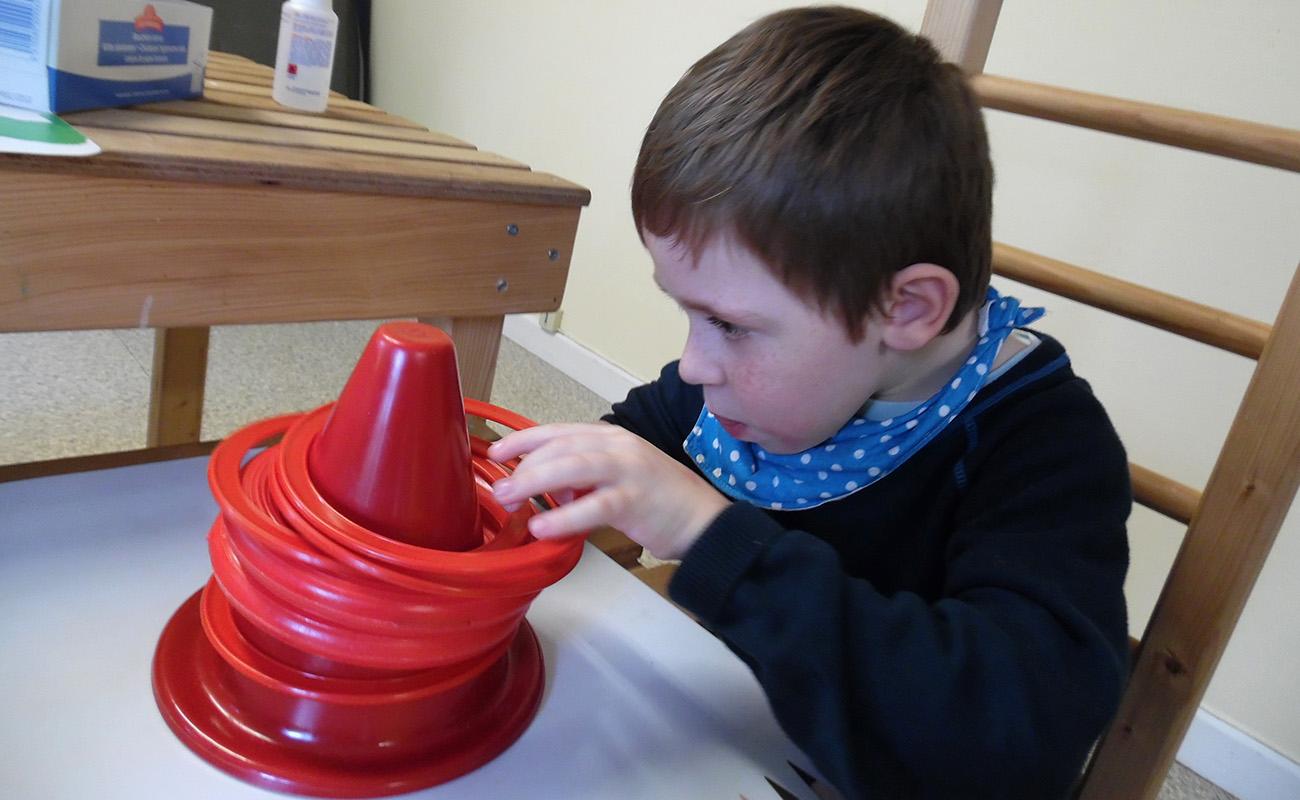 Enfant handicapé moteur jouant avec des cerceaux et un plot participant de la Pédagogie Conductive .